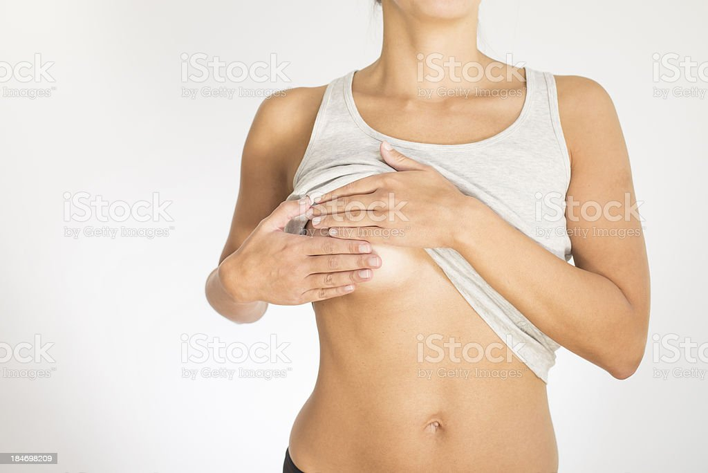 Woman testing her breast for cancer stock photo