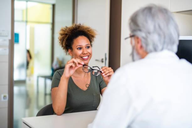 Frau testet ihre neue Brille im Augenarzt – Foto