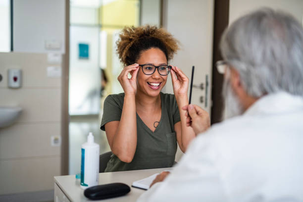 woman testing out her new eyeglasses in ophthalmology office - optometrist stock pictures, royalty-free photos & images