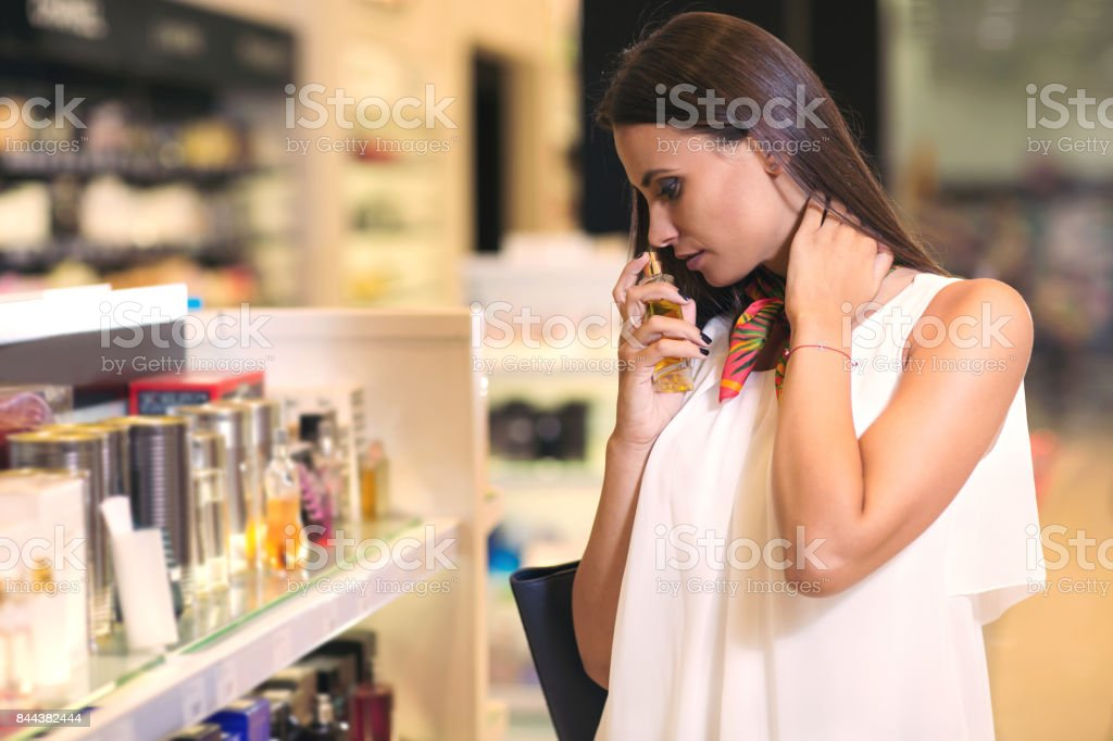 Woman testing perfumes in cosmetics store stock photo