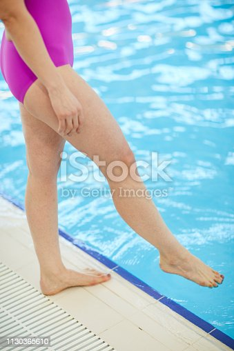 Low section portrait of unrecognizable senior woman wearing swimsuit testing pool water, copy space