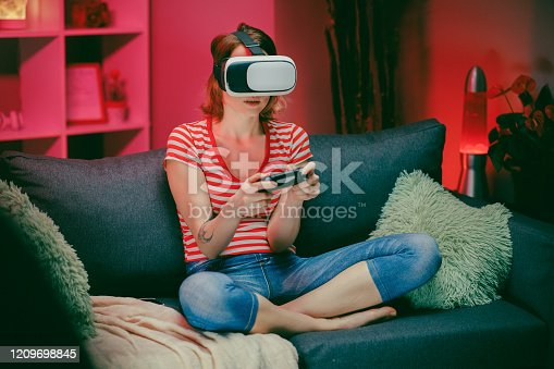 istock Woman testing virtual reality glasses while sitting on sofa in home interior. Caucasian female with vr headset on face playing game with smile on couch in modern apartment 1209698845
