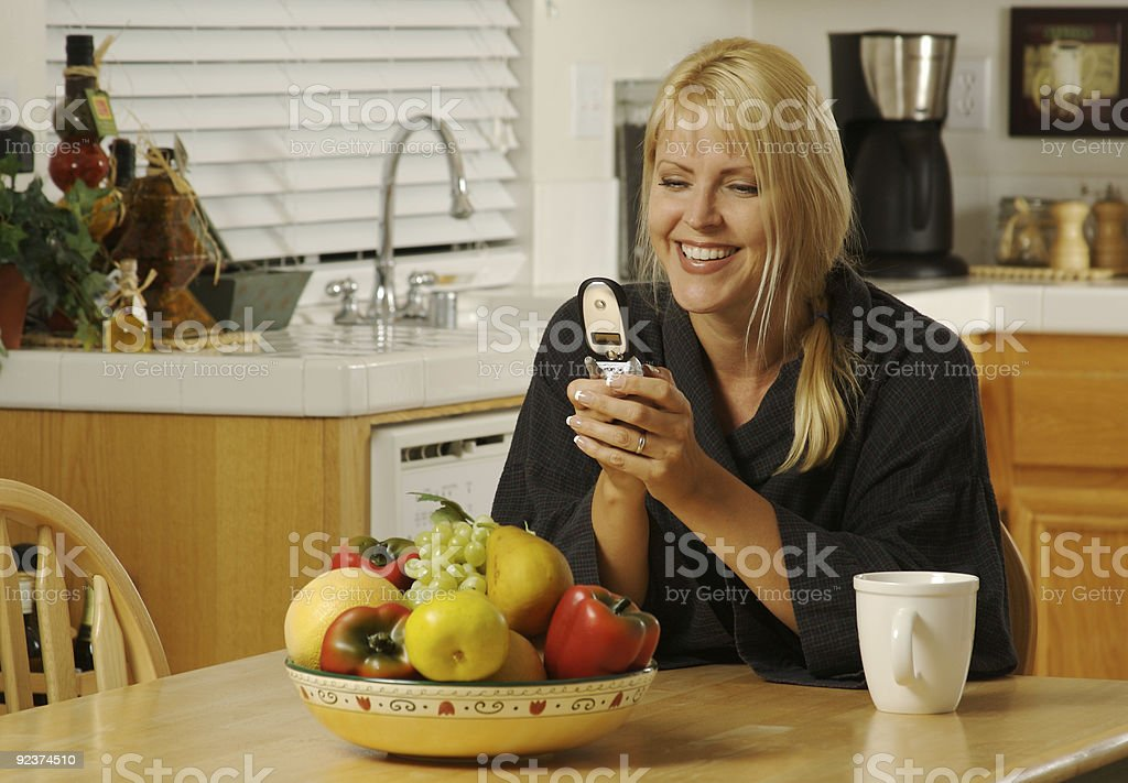 Woman Texing with Cell Phone in kitchen. royalty-free stock photo