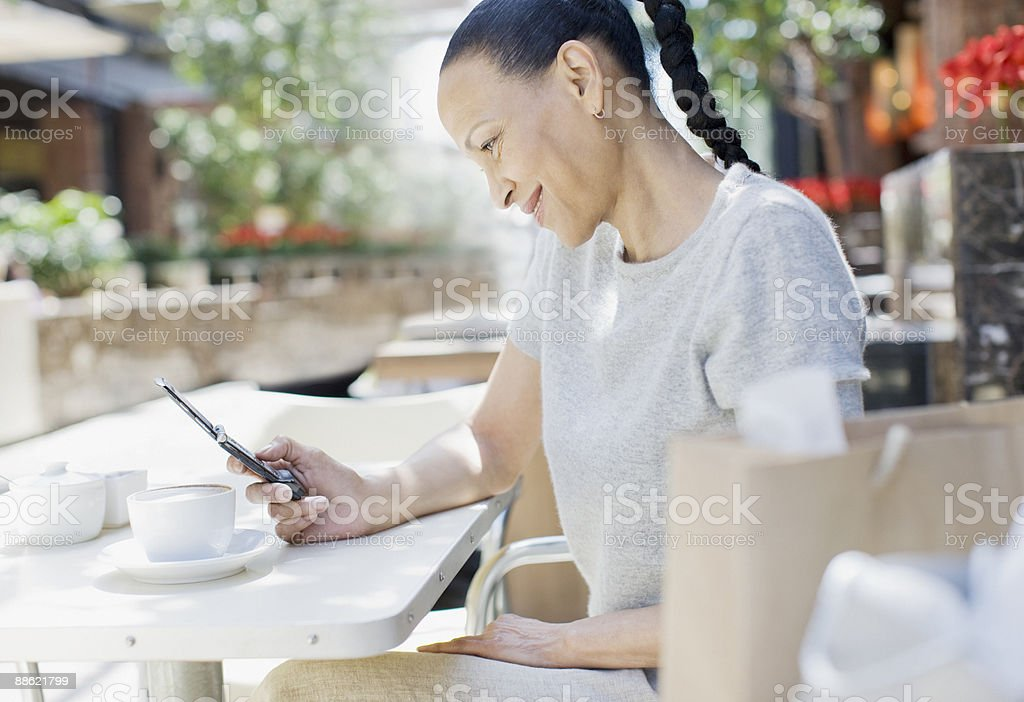Woman text messaging at cafe royalty-free stock photo