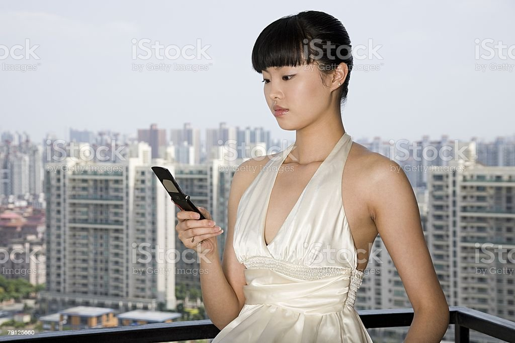 Woman text messaging on balcony 免版稅 stock photo