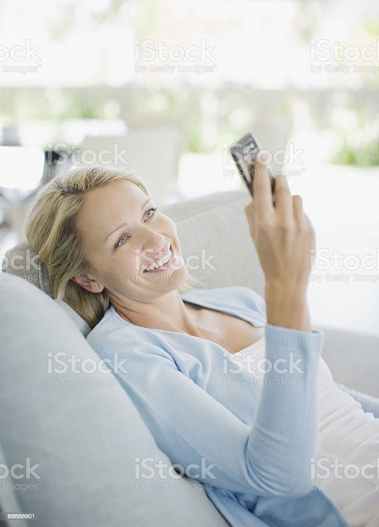 Woman text messaging on cell phone in living room royalty-free stock photo