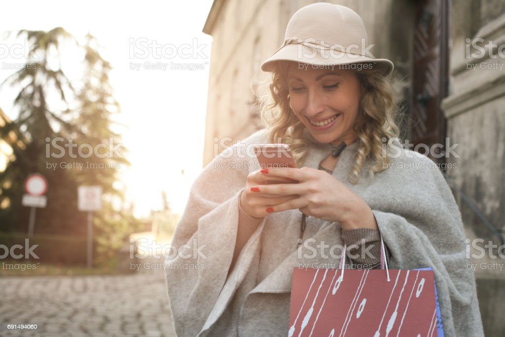 Woman text messaging. Woman using smart phone outdoor. stock photo