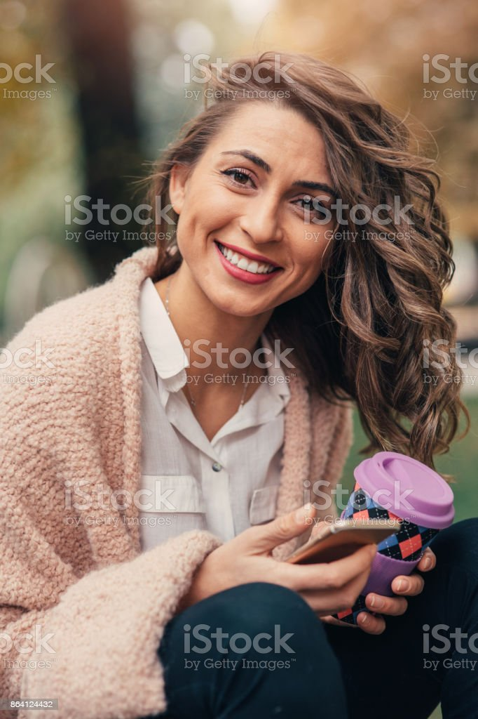 Woman texting and drinking coffee in the park royalty-free stock photo