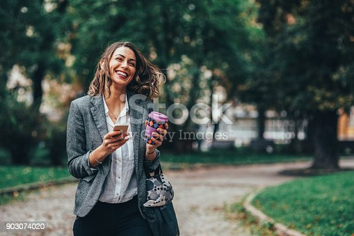 Beautiful woman drinking coffee while taking a walk in the park.