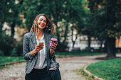 istock Woman texting and drinking coffee in the park 903074020