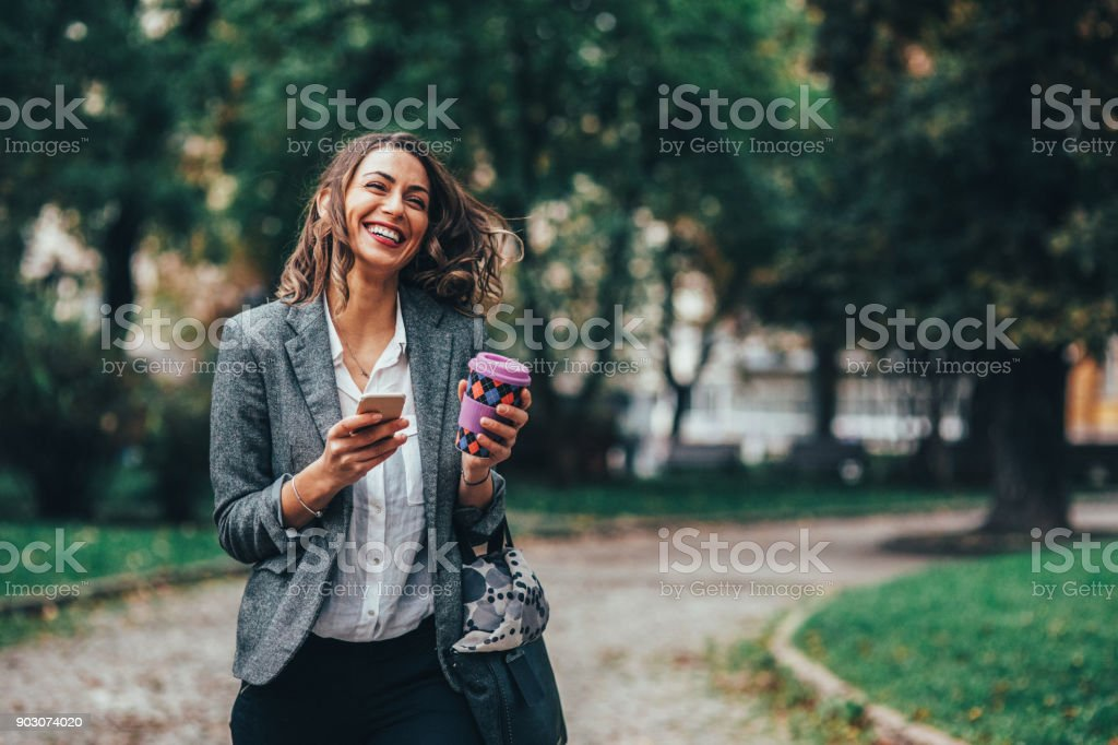 Woman texting and drinking coffee in the park stock photo