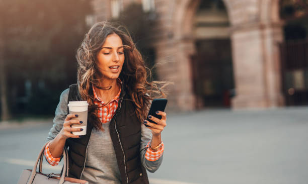 Woman texting and drinking coffee outdoors. stock photo