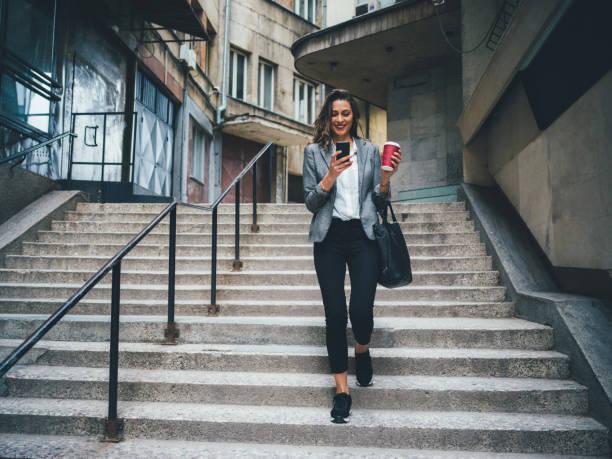 vrouw texting en drinken koffie buitenshuis - business woman phone stockfoto's en -beelden