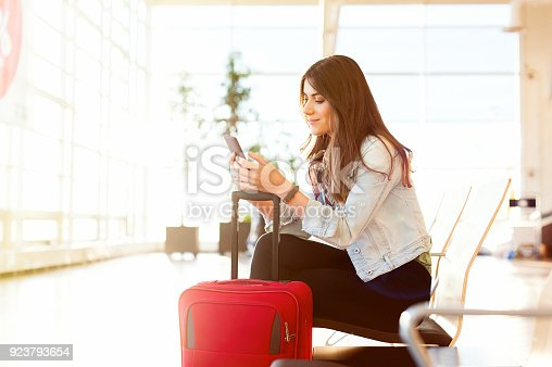 istock Woman texting and using phone before getting on the plane 923793654
