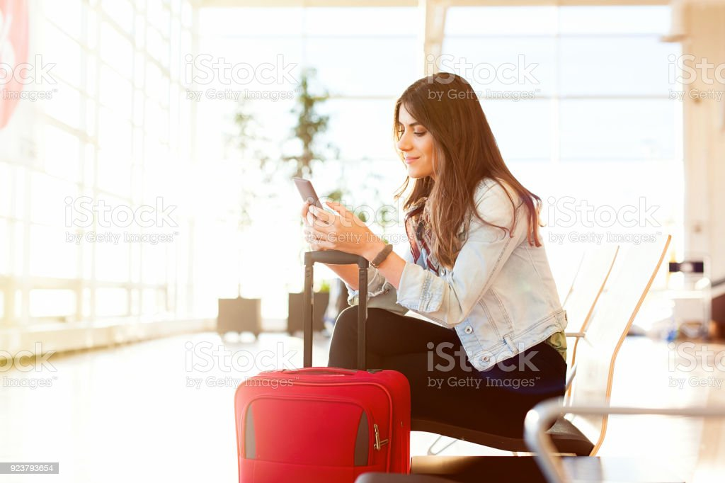 Woman texting and using phone before getting on the plane stock photo