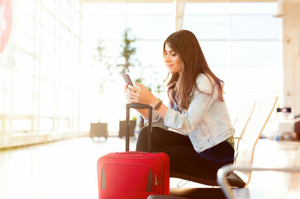 woman texting and using phone before getting on the plane - airport stock photos and pictures