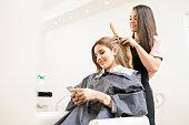 istock Woman texting at a hair salon 692971156