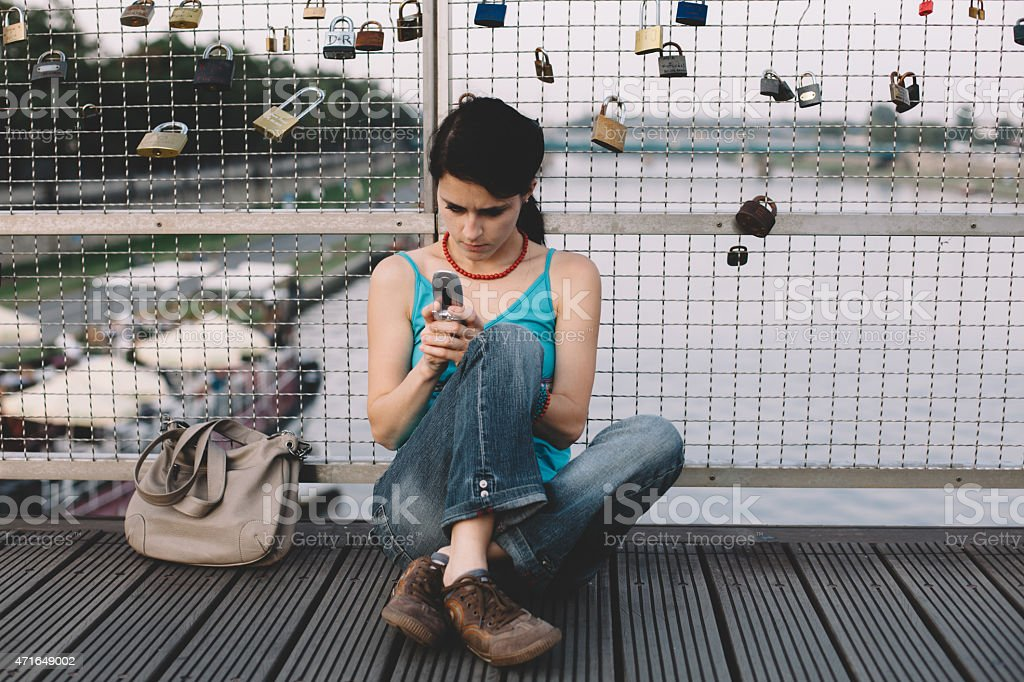 Woman texting messaging at the bridge stock photo