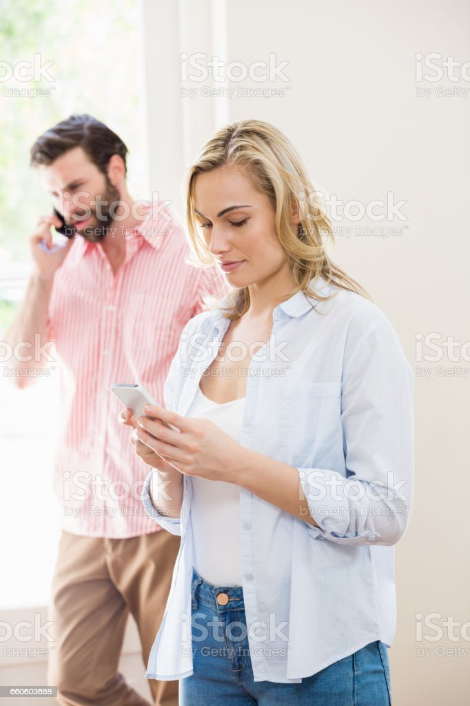 Woman texting messaging while man talking on mobile phone royalty-free stock photo