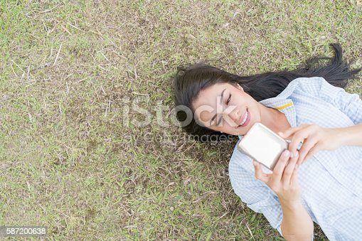 istock Woman texting on her cell phone at the park 587200638