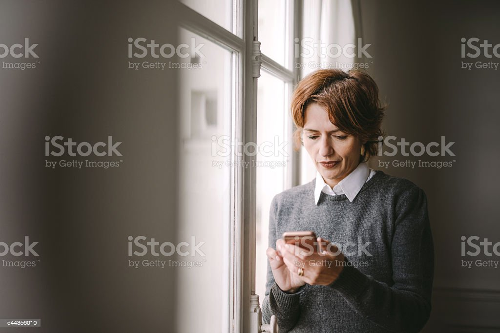 woman texting on her mobile phone stock photo