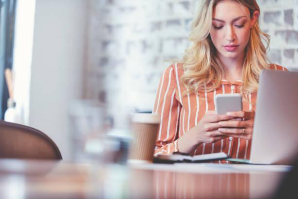 Frau textet auf ihrem Handy. Sie ist konzentriert und ernst. – Foto