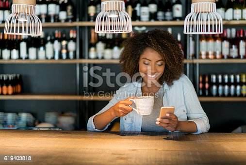 Happy African American woman texting on her cell phone while having a cup of coffee at a cafe