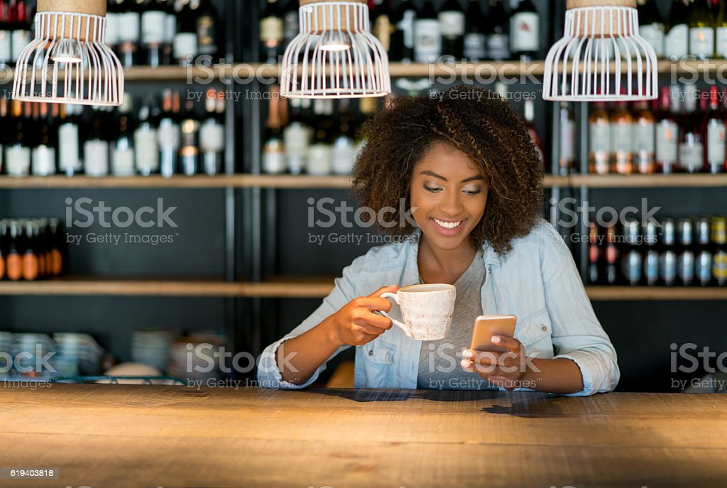 Woman texting on her phone at a cafe stock photo