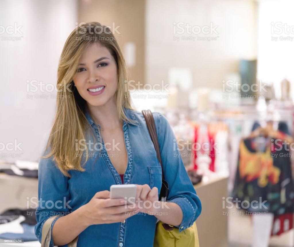 Kvinna textning på hennes telefon medan shopping - Royaltyfri Affärscentrum Bildbanksbilder