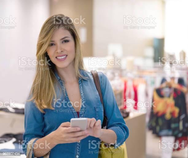 Kvinna Textning På Hennes Telefon Medan Shopping-foton och fler bilder på Affärscentrum