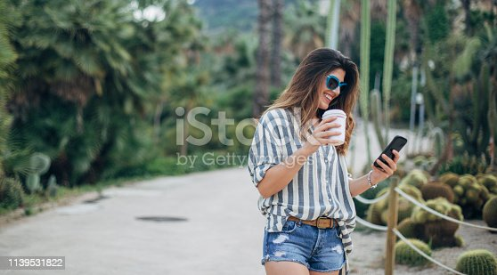 Beautiful woman using phone and holding cup of coffee in botanical garden