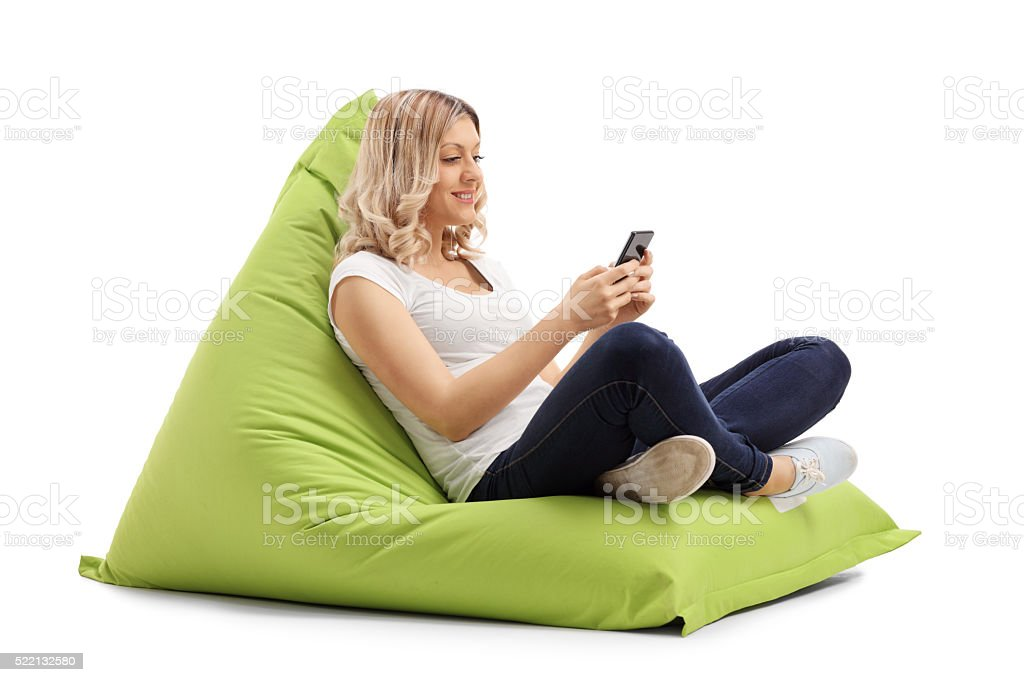 Woman texting on phone seated on beanbag stock photo