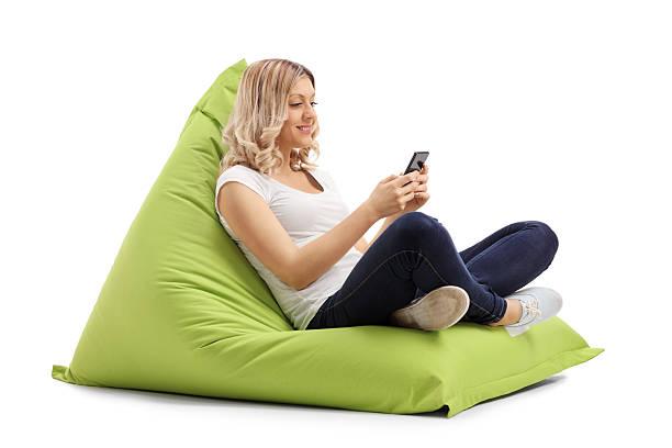 frau sms auf handy sitzen auf dem sitzsack - stuhlpolster stock-fotos und bilder