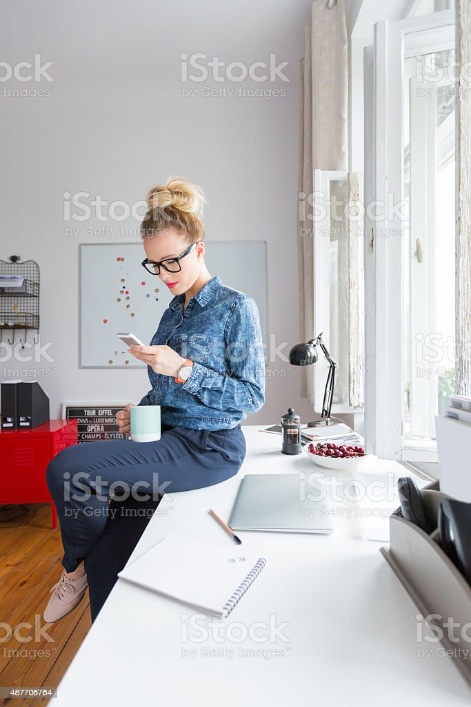 Woman texting on smart phone in an office Blonde woman wearing jeans shirt and nerd glasses sitting on the desk in an office and texting on smart phone, holding cup of coffeee in hand. 2015 Stock Photo