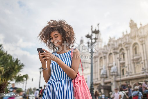 Young woman texting on smart phone against National Theater of Cuba. Beautiful female is smiling while traveling in city. She is in striped blue dress.