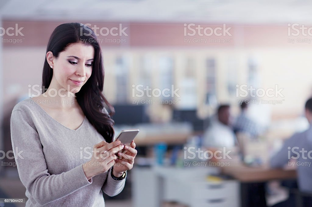 Woman texting on smart phone in office stock photo