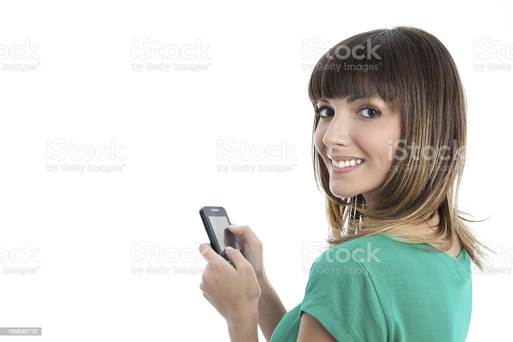 Woman texting on smartphone looking over her shoulder royalty-free stock photo