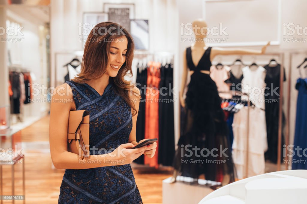 Woman texting on the phone in a clothing store stock photo