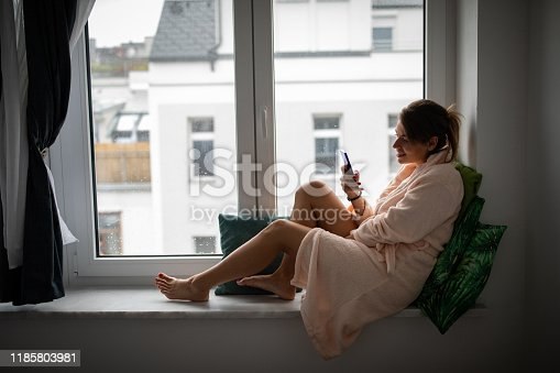 Beautiful young woman at home, sitting on window sill and using phone