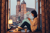 istock Woman texting on the window sill 503162468