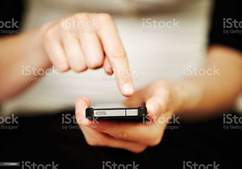 Woman texting or dialing out on an smartphone royalty-free stock photo