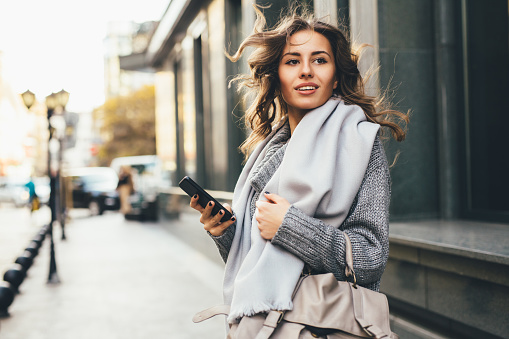 A young woman texting on the phone outdoor in the city.