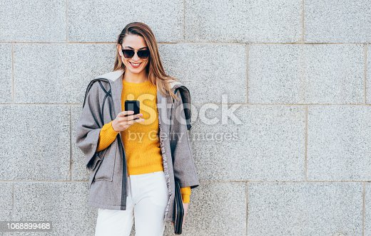 Woman texting leaning on the wall outdoor