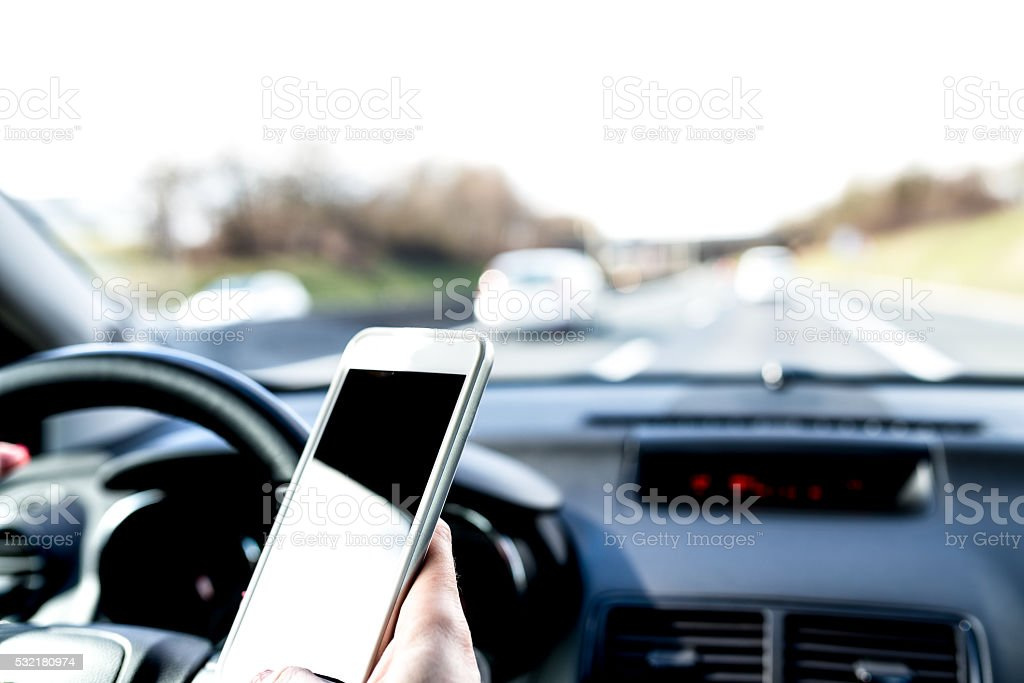 Woman texting while driving stock photo