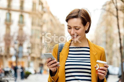 Mid adult woman texting on mobile phone while holding disposable cup. Smiling pedestrian is wearing casuals. Female is walking in city.