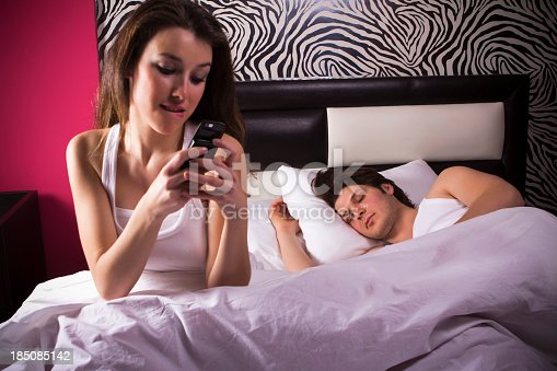 istock Woman texting while in bed with sleeping man 185085142