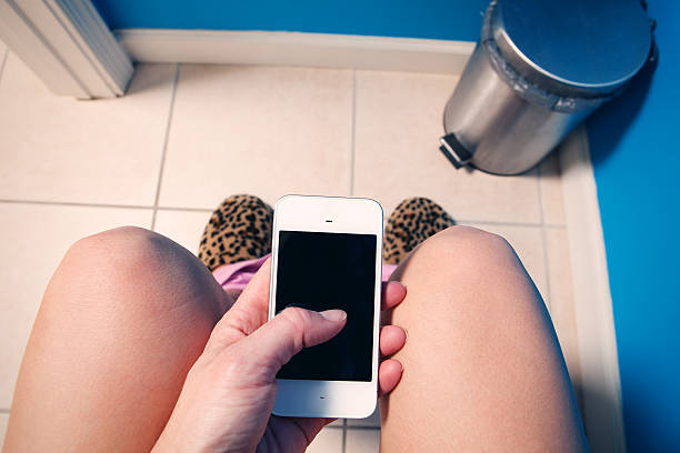 woman texting while using the restroom - cell phone toilet stockfoto's en -beelden