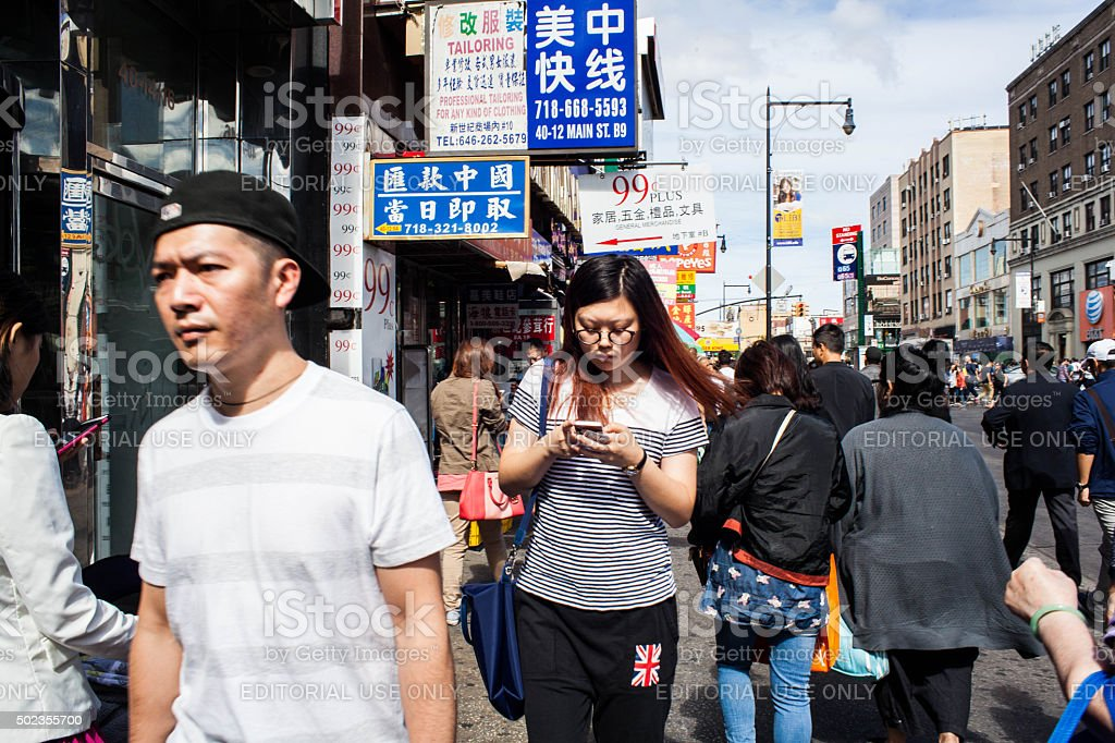 Woman texting while walking down Main Street in Chinatown stock photo