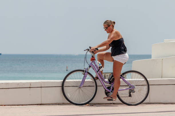 Woman texting with smart phone on bicycle stock photo