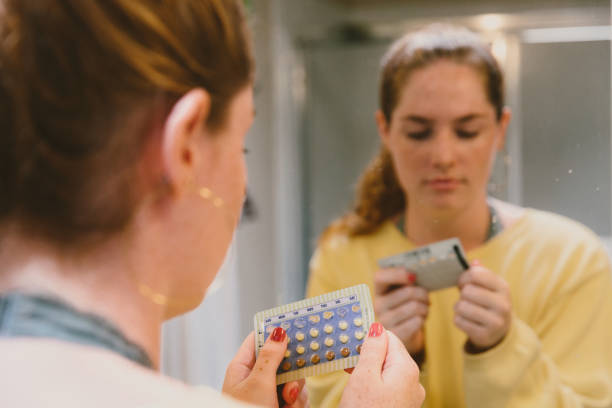 Woman Thinking About Her Health With Birth Control Pills Woman in mirror examining birth control pills. contraceptive stock pictures, royalty-free photos & images
